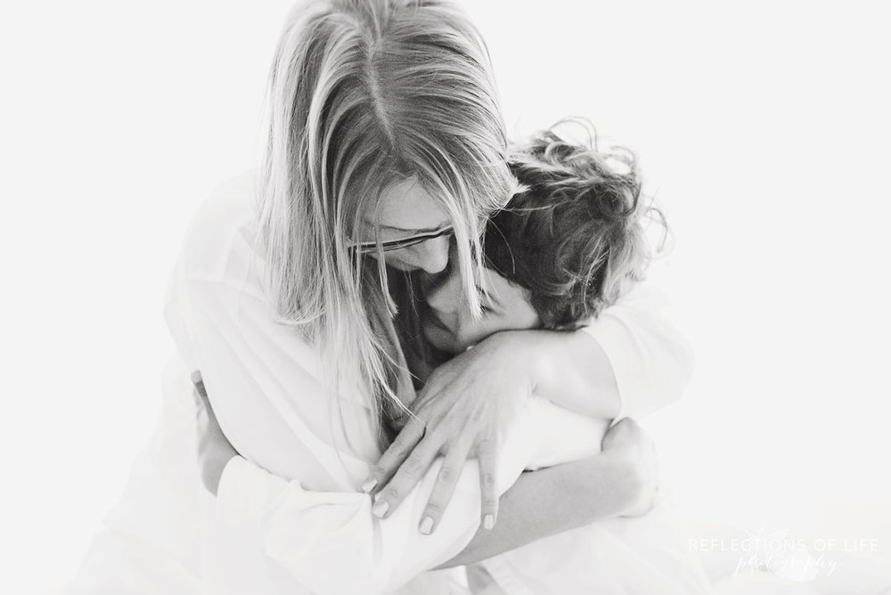 portrait of mom and son hugging black and white
