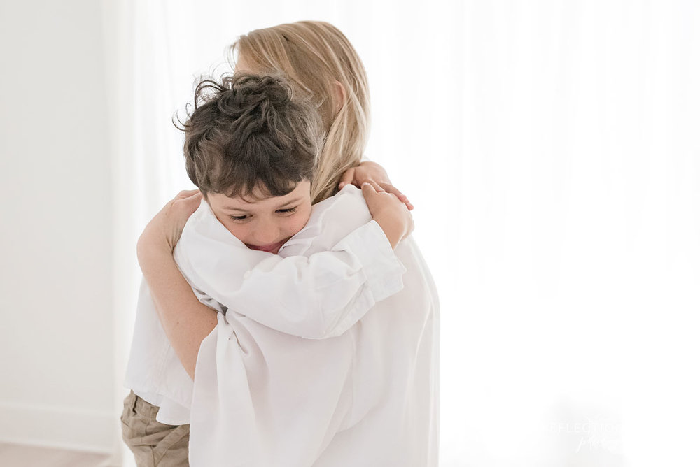 young boy and mother hugging in studio white background