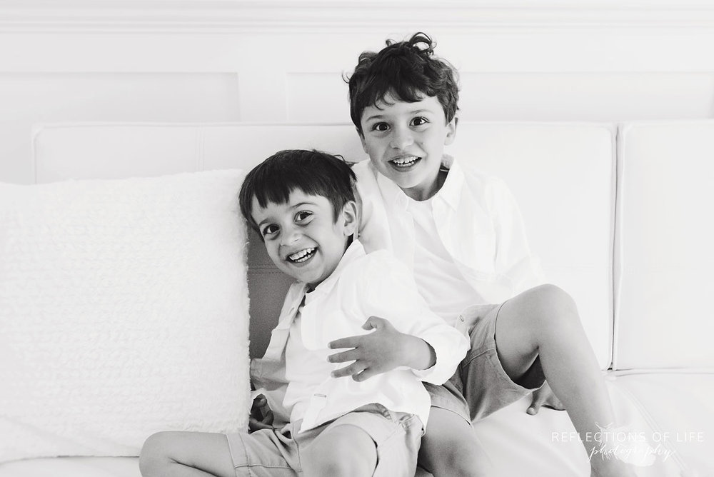 black and white portrait of two young boys sitting on white couch