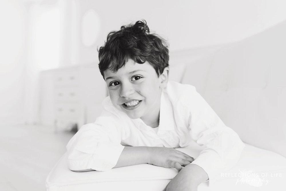 black and white portrait of boy laying on couch smiling