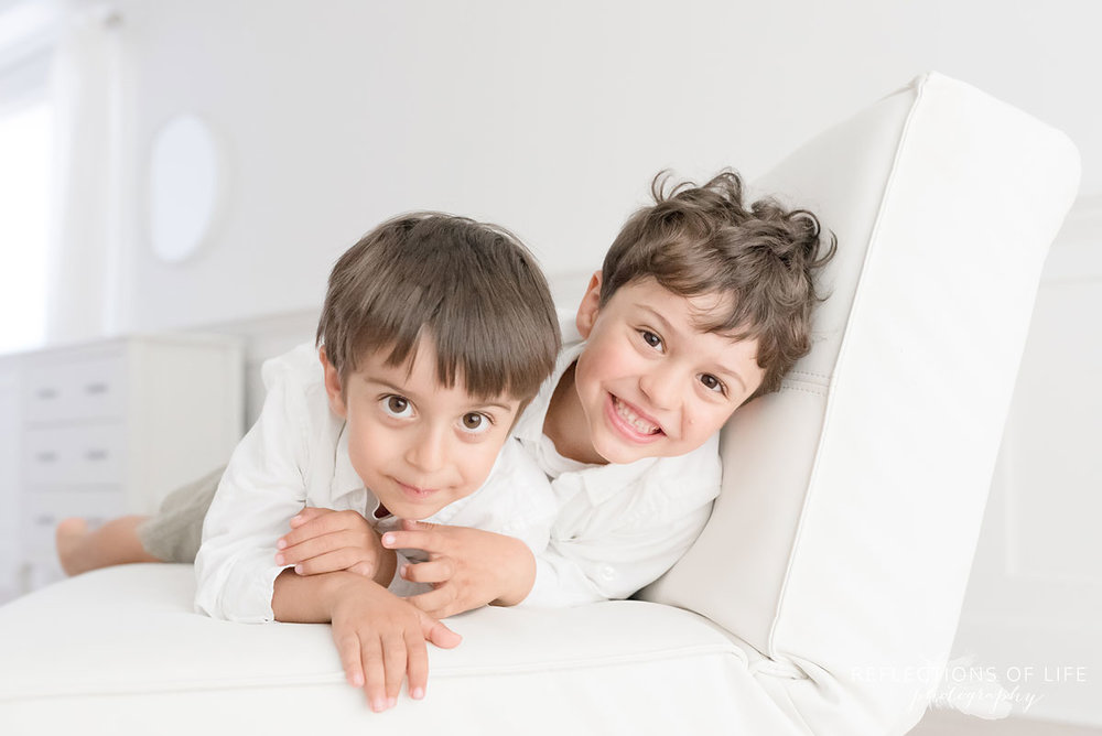 portrait of two brothers on white couch smiling