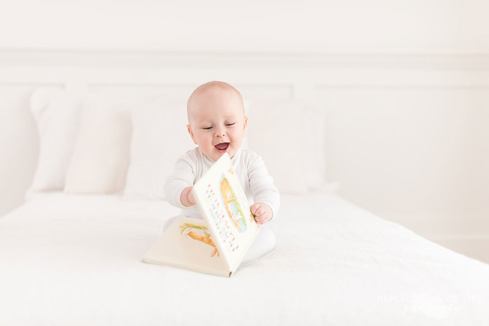 baby boy laying on white bed with book.jpg