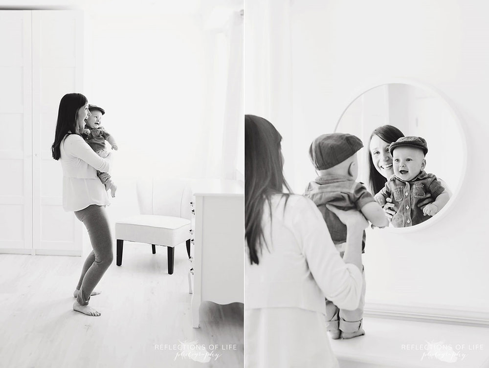 mom lifting baby boy to look in mirror black and white.jpg