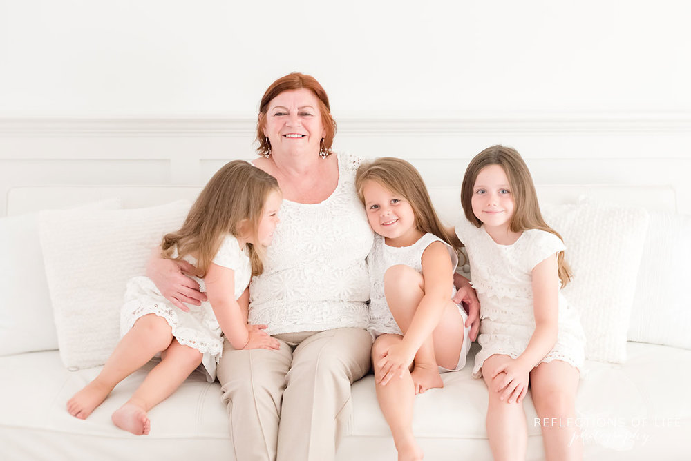Gorgeous Grandma sitting with her granddaughters in a white natural light studio