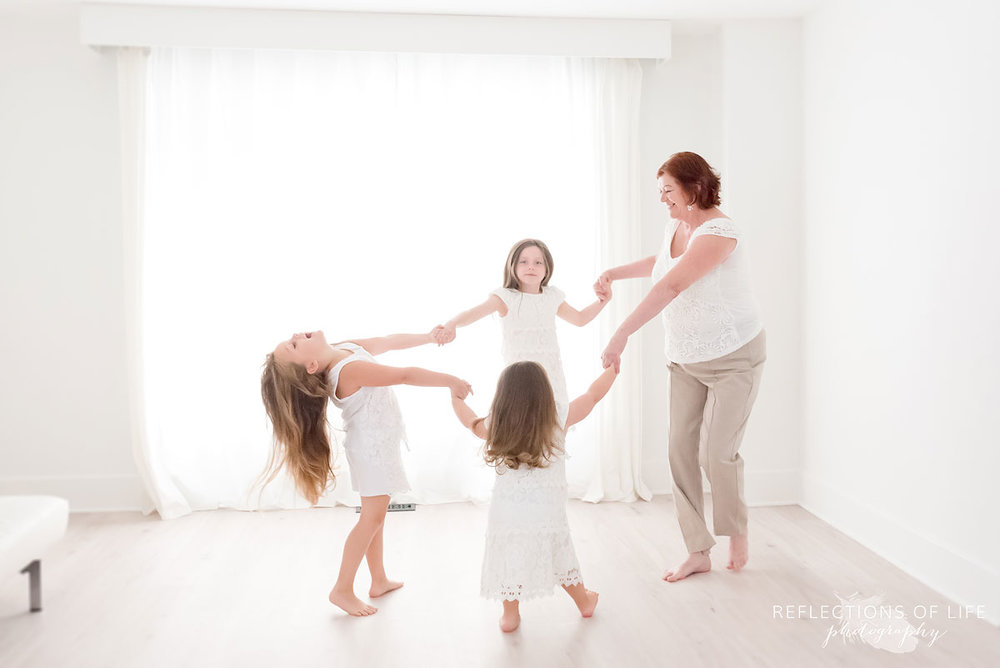 Grandma and granddaughters dancing by the window in natural light studio