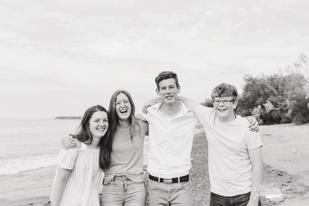 Fun sibling shot of everyone smiling and laughing by the beach in Niagara Ontario