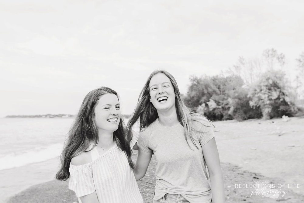Sisters laughing in black and white at the beach