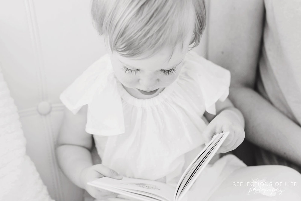 litttle girl reading a book in black and white