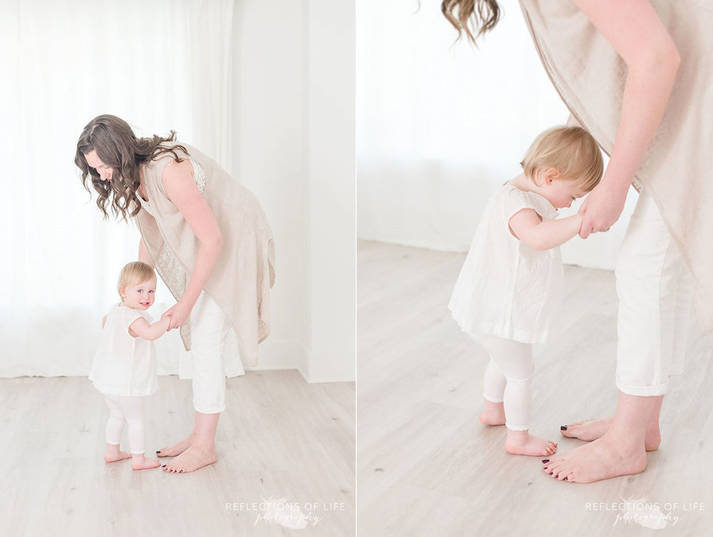 mom teaches one year old daughter to dance in the photo studio