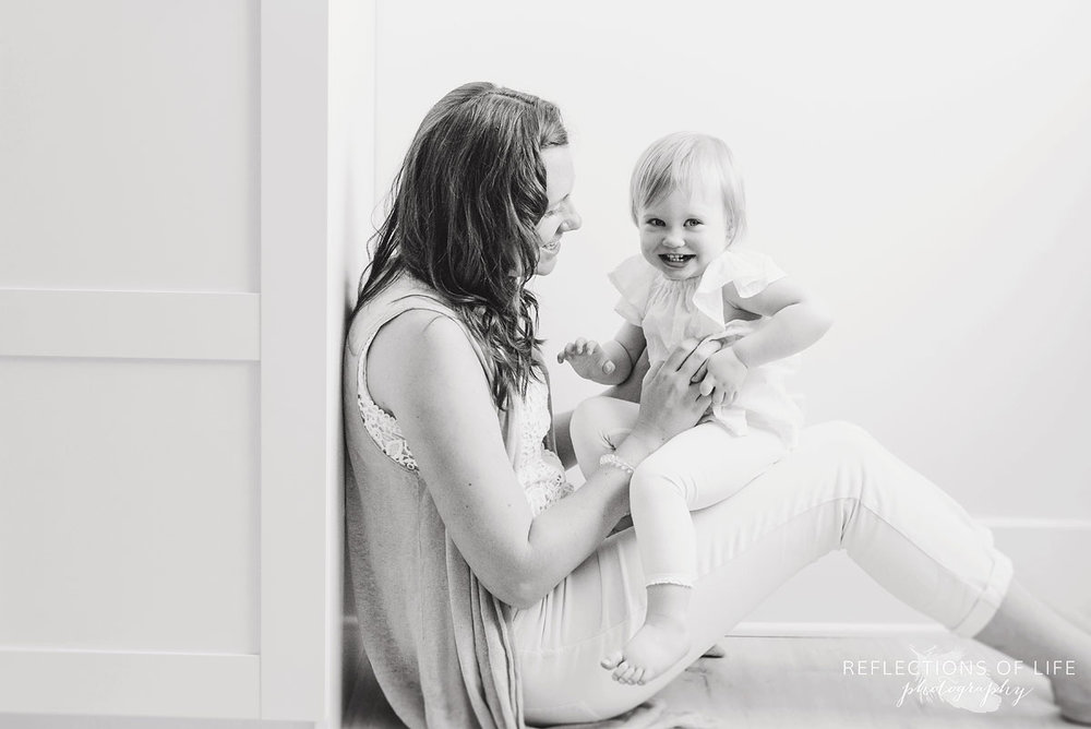 mom tickles her baby girl in black and white