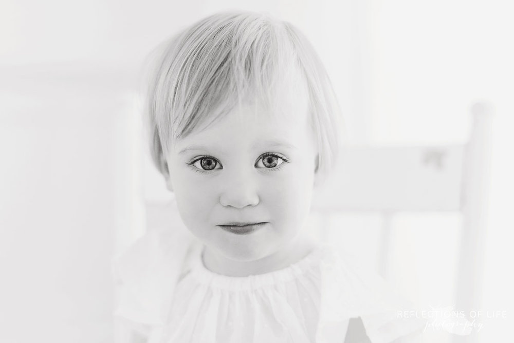 little girl looking straight into the camera in black and white