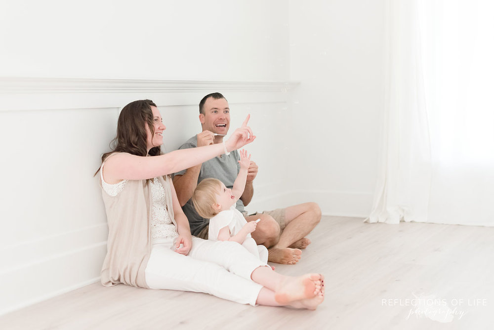 mom and dad blow bubbles with their daughter in natural light studio
