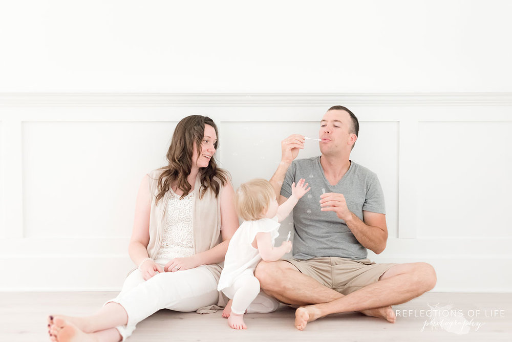 dad blows bubbles for his little girl in neutral light studio