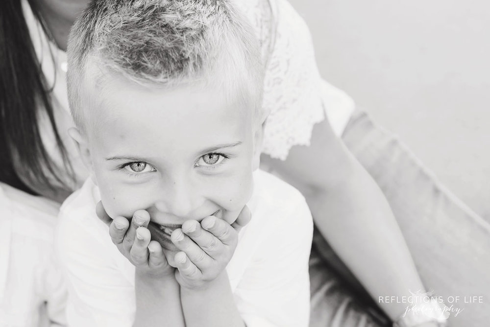 little boy covering his mouth with his hands in black and white
