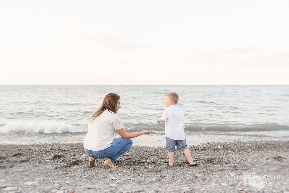 Mom handing her son a rock at Casablanca Beach in Grimsby