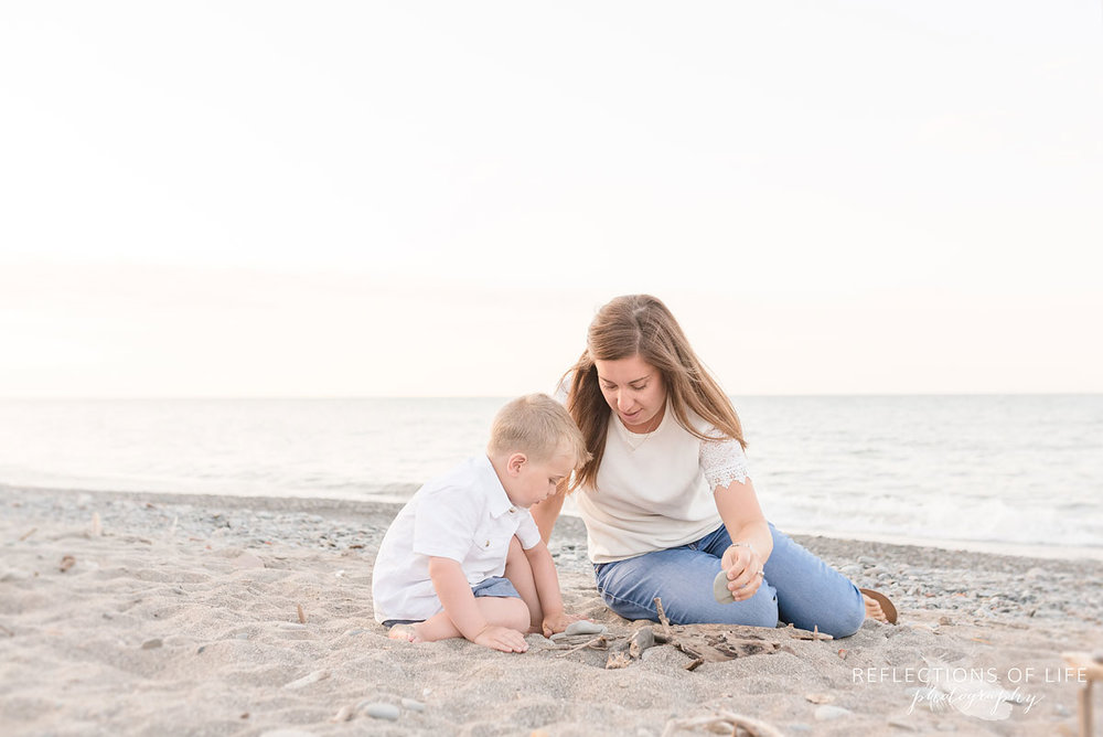 Little boy sitting with his mama at the beach in Grimsby