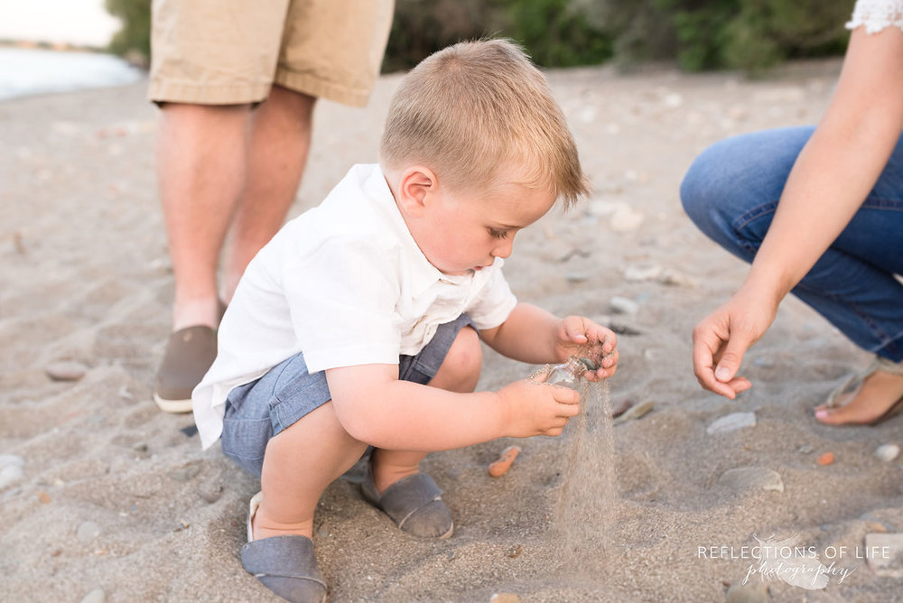 Little boy playing with sand at Grimsby Beach