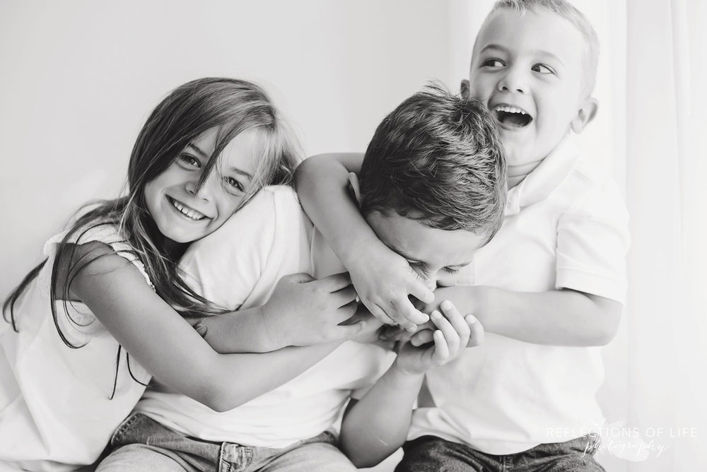three siblings playfight for the camera