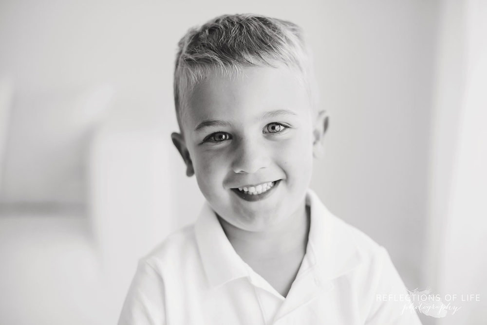 little boy smiling in black and white