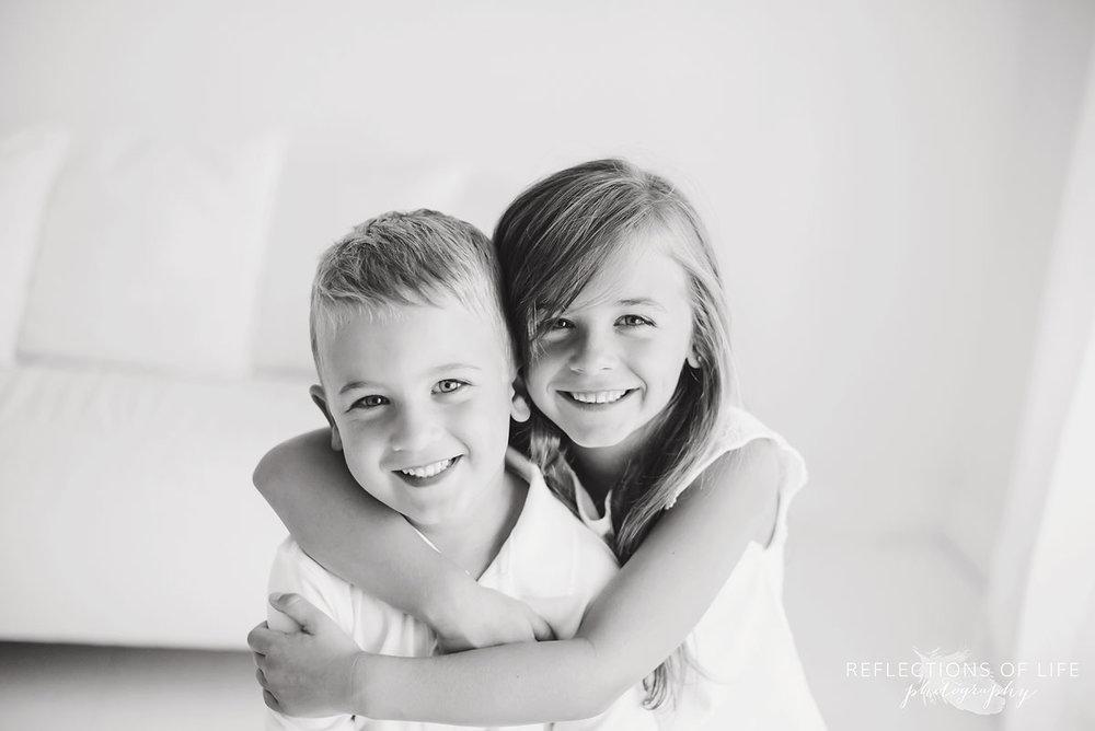 siblings hugging for the camera