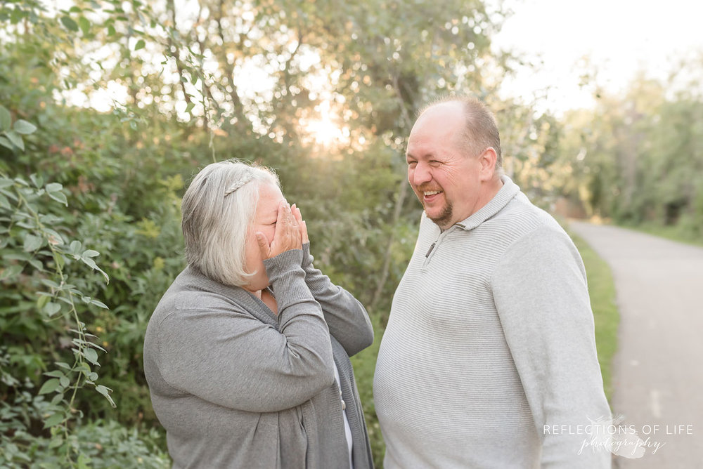 Husband and wife laughing with each other in nature setting