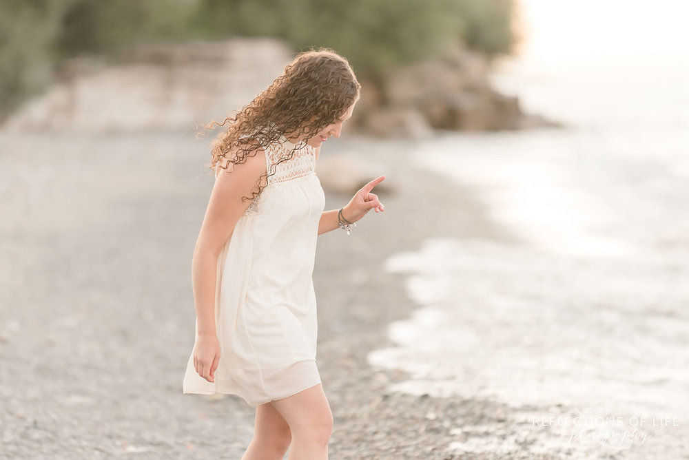 Girl walking along the beach with white dress