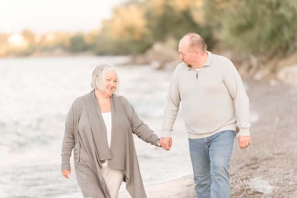Husband and wife holding hands and walking along the beach in Niagara Region