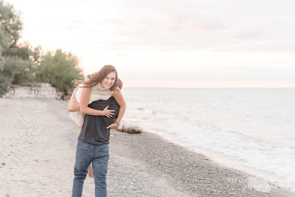Boyfriend carrying girlfriend along the beach