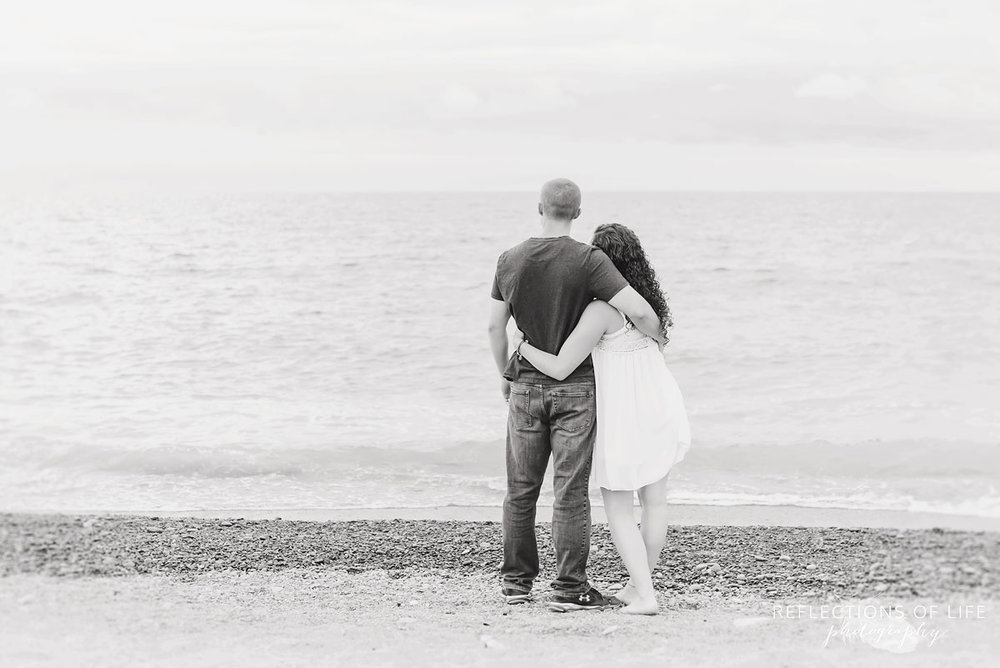 Black and white of girlfriend and boyfriend looking at the water on the beach