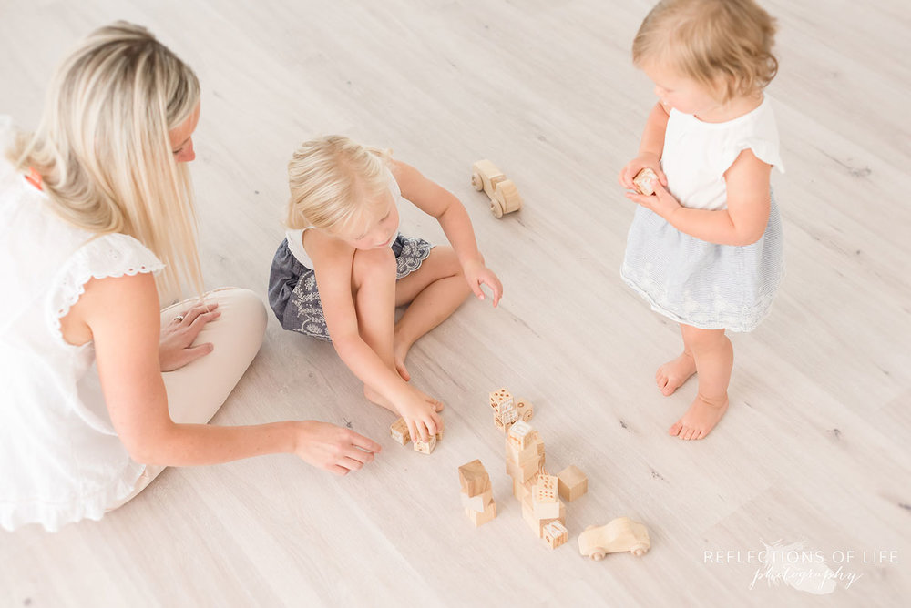 Mom and daughters playing with blocks in Niagara Region