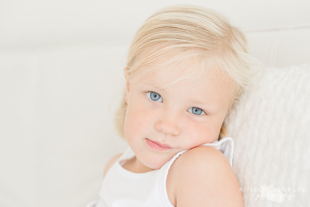 Little girl with blonde hair in white studio