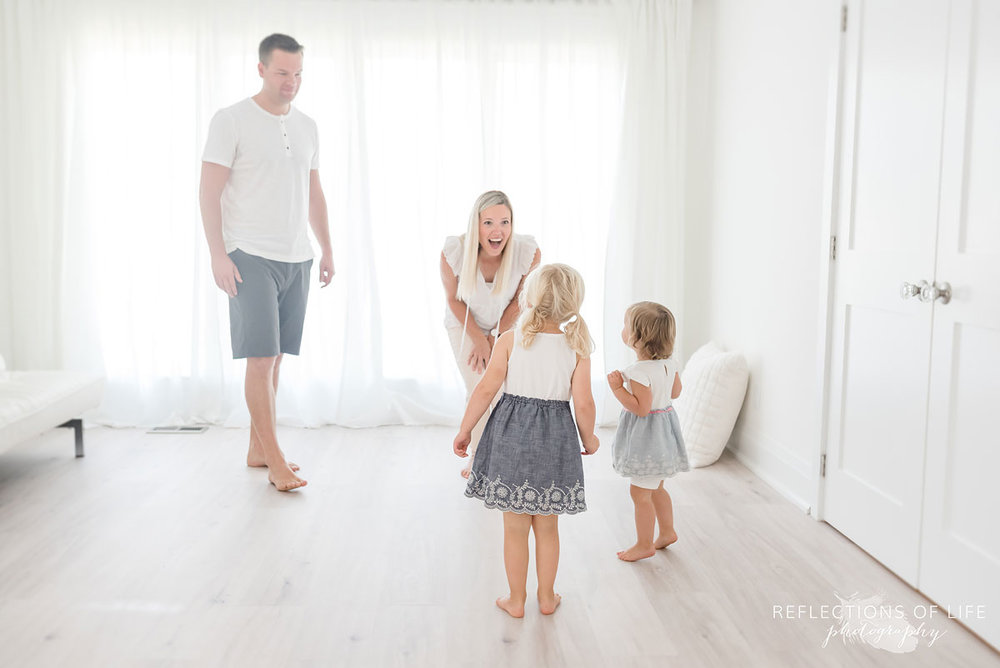 Family of four playing in white studio