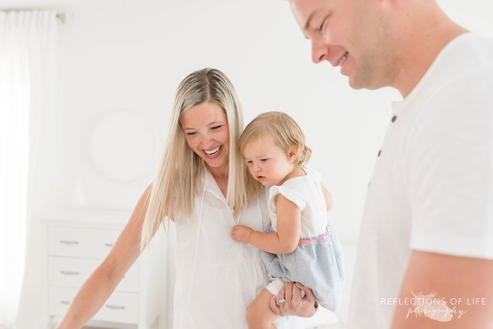 father mother and daughter in white studio Grimsby Ontario