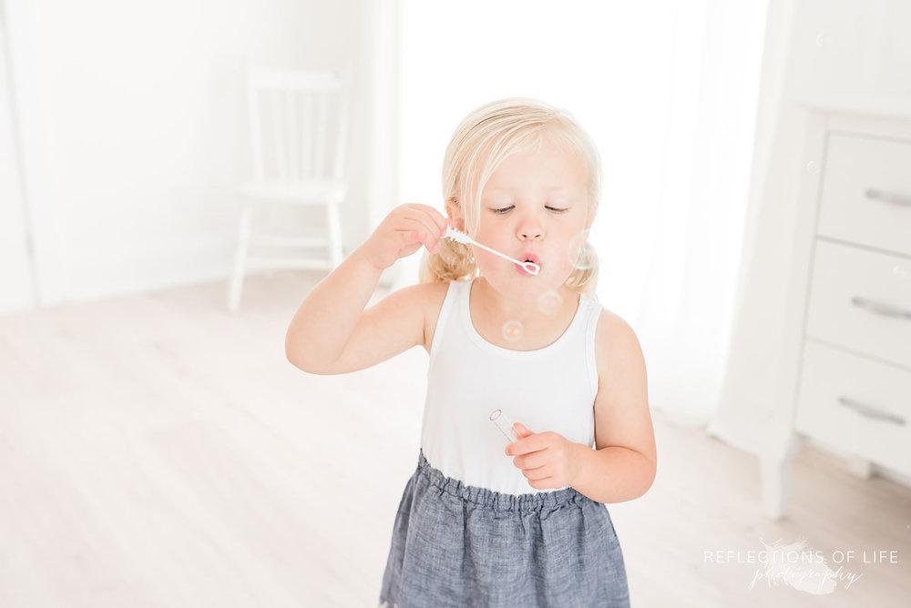 little girl blowing bubbles in white studio