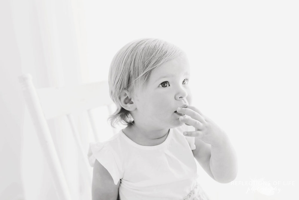 black and white of young girl in white studio
