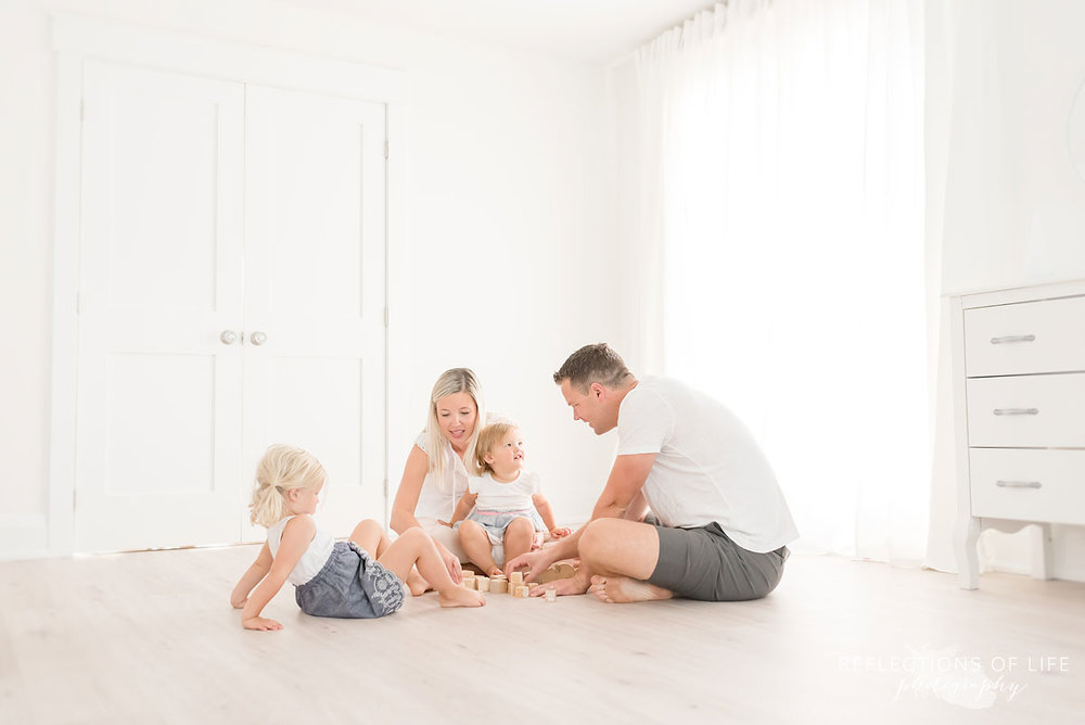 family playing in white studio
