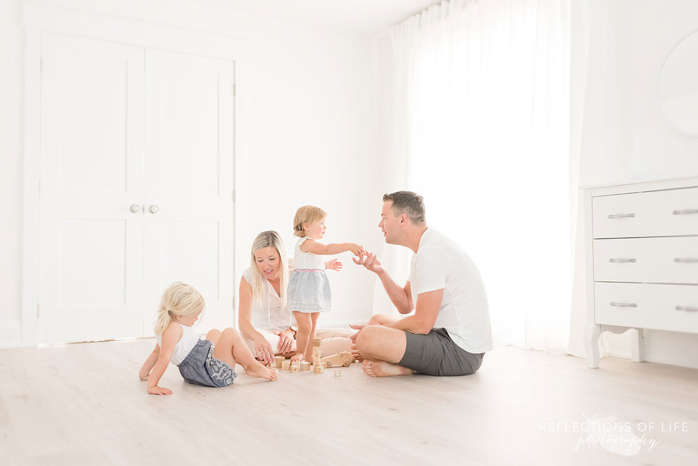 family playing in white studio with blocks