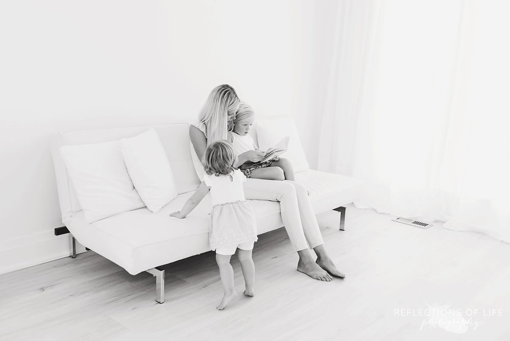 black and white of mom and daughters reading a book