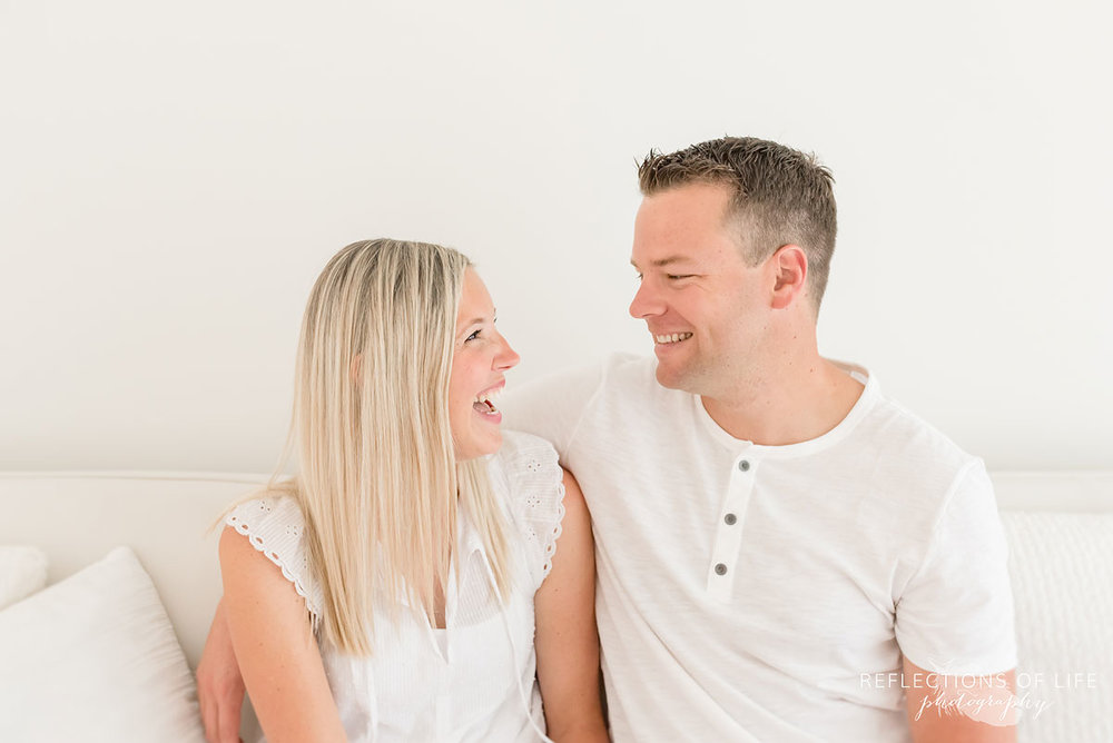 husband and white laughing on white couch