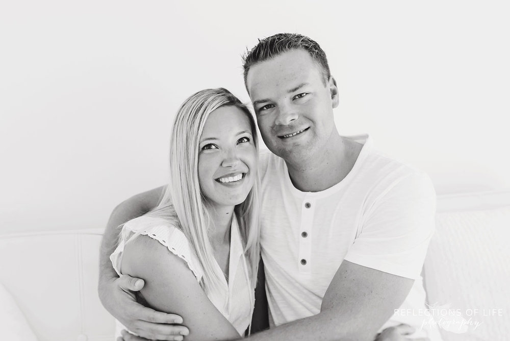 black and white of couple on white couch in white studio