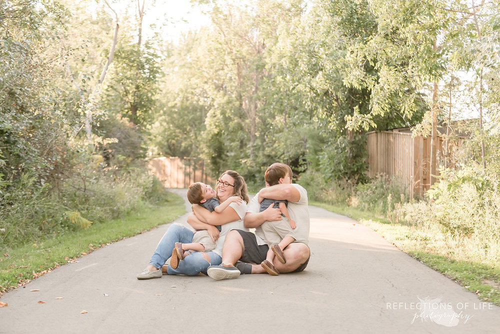 Family of four sat on a path hugging