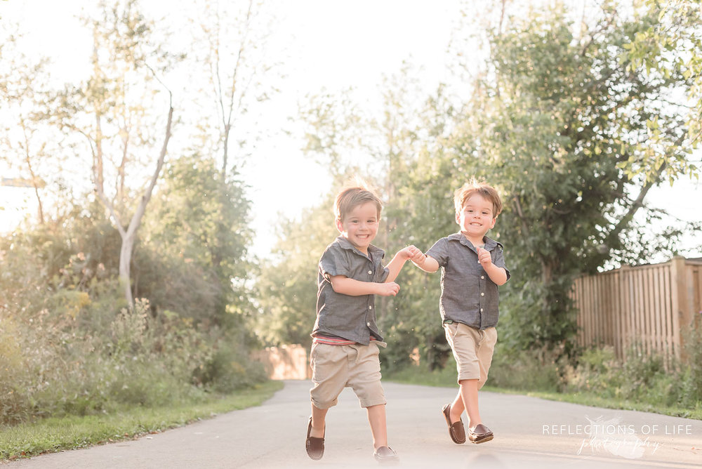 Two boys running down a path and holding hands