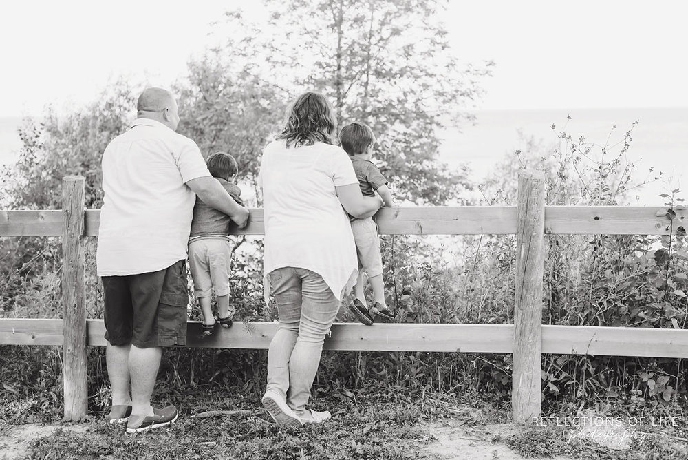 Family of four looking out at lake in Grimsby Ontario black and white