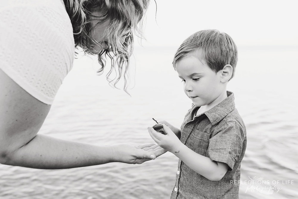 Mother holding her hand out looking at son who is holding a rock black and white
