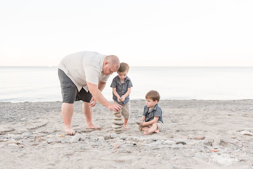 Father and two sons building a rock tower on Grimsby Beach