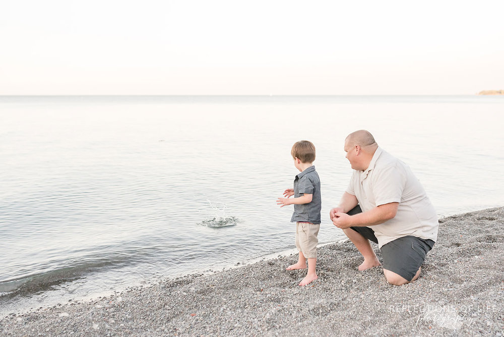 father and son throwing rocks into the water