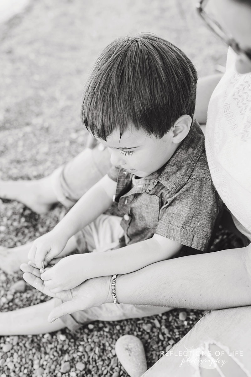 mom and son sitting together on the beach playing with stones black and white