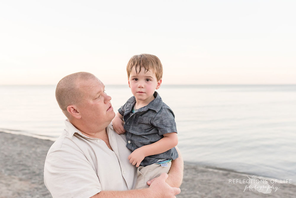 a dad holding his son on Grimsby Beach in Ontario