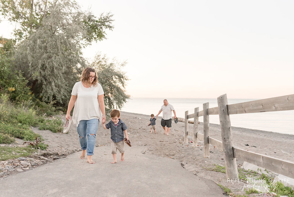 family of four walking up pathway off the beach holding hands