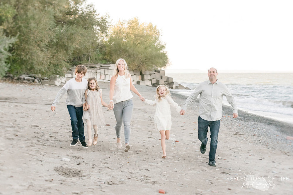 family holding hands running on beach
